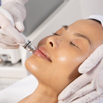 Beautiful Asian woman receives a facial aesthetic treatment from a medical professional.